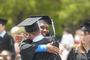 Graduates hug after receiving their diplomas.<em><span style=font-size:9pt;>&nbsp;Credit: Bob MacDonnell</span></em>