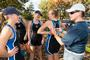 Chatting with the rowers from Boat A, women's rowing coach Eva Kovach helps Caity Sprague '13 pin the boat number to her unisuit.