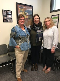 Lillian Liebanthal, Melissa Shafner, and Julia Kaback pose in from of a poster from the Ability Exhibit in the Accessibility Office!