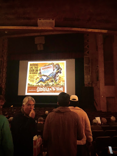 Inside The Garde Theater on stage is projected a poster from a Godzilla remake