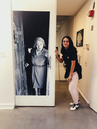 Student Dani Maney poses with a life-sized photograph of the Nut Museum founder