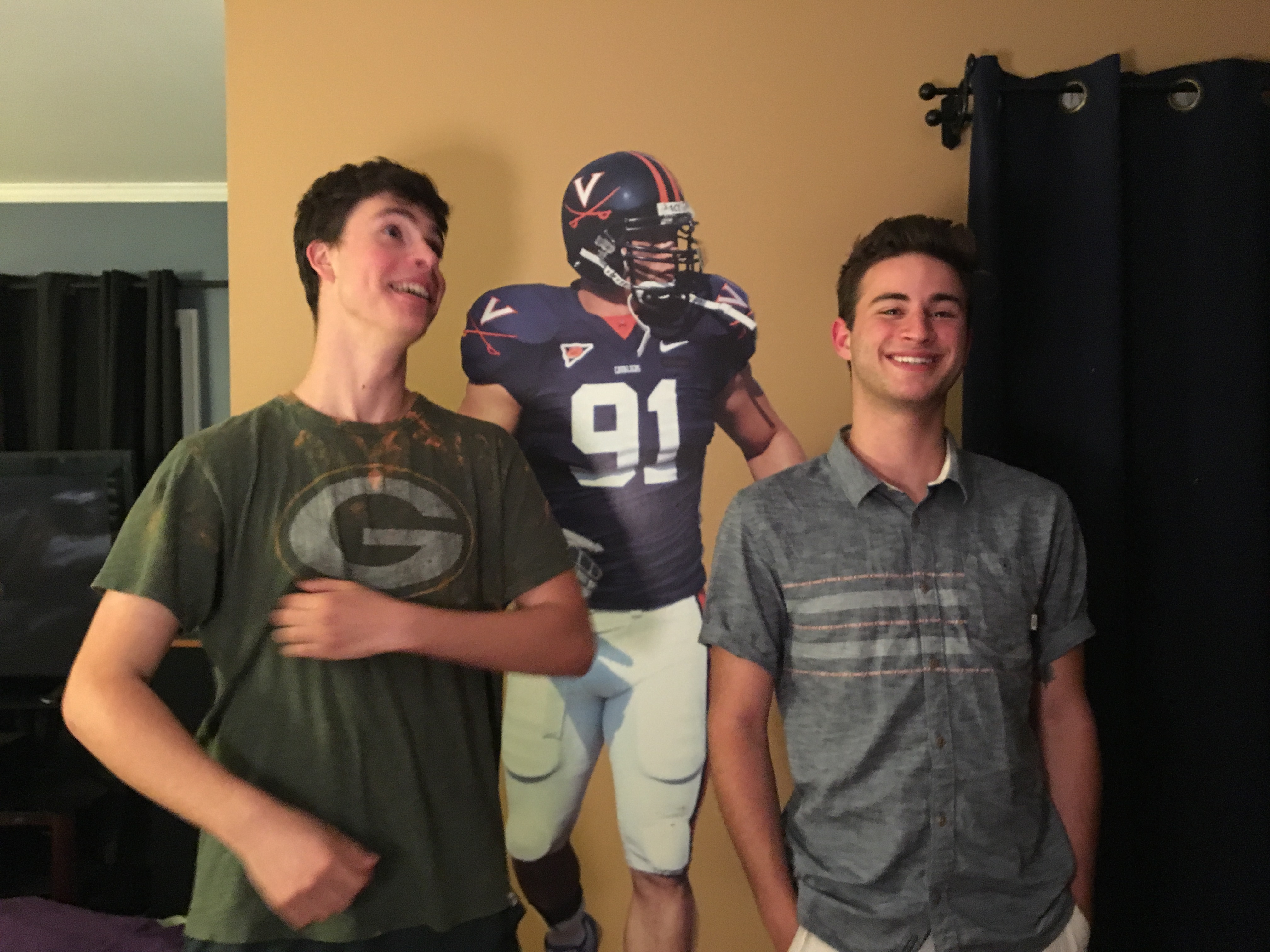 Mark and Samuel pose in front of a stick on wall graphic of a University of Virginia football player