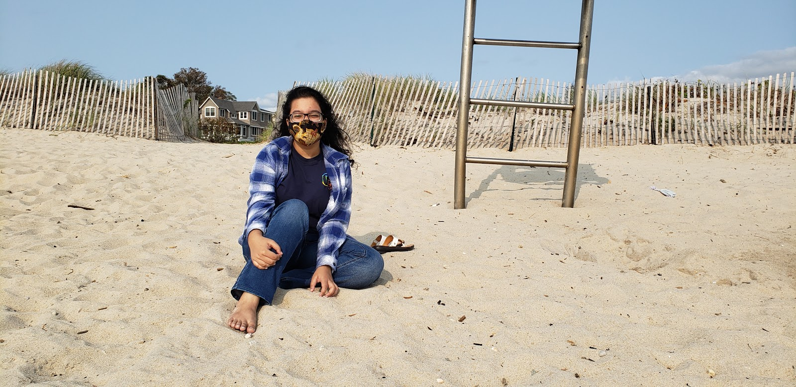 Samirah sits cross-legged in the sand at the beach with her mask on.