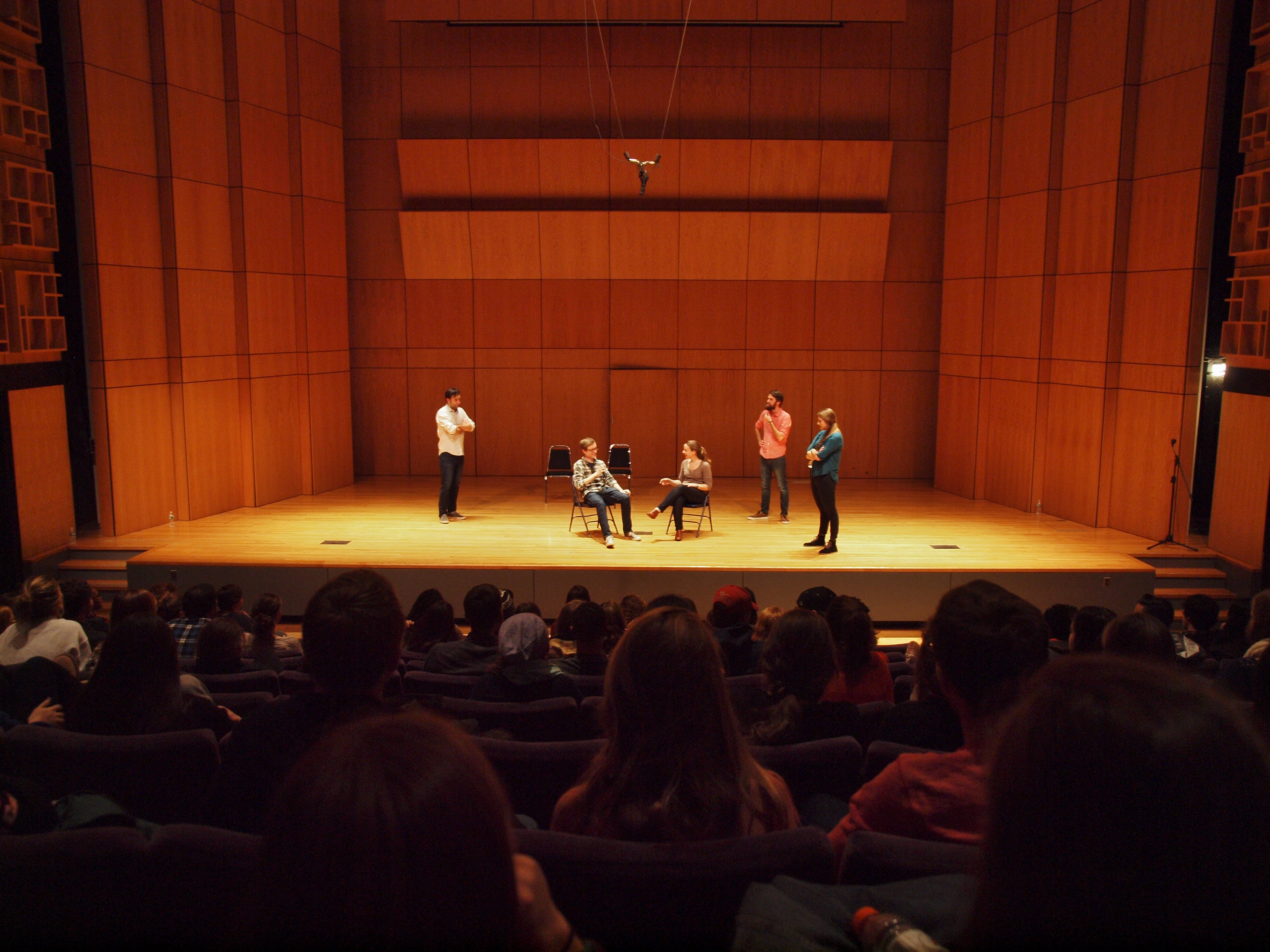 An improv groups interviews a student on stage