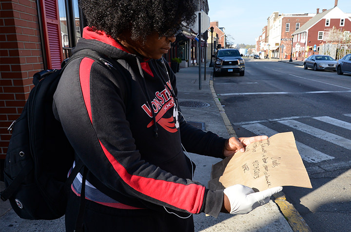 Wynndee Reese '13 examines an abandoned cardboard sign while documenting discarded ephemera on the streets of New London as part of collaborative research in Anthropology 482 (Archaeology of the Contemporary).