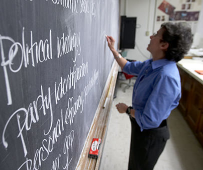 MaryAnne Borrelli, professor of government, writes on the board during a lecture.