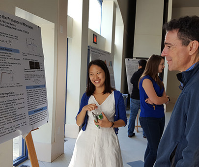 A physics student with her presentation board at the Science Research Symposium.
