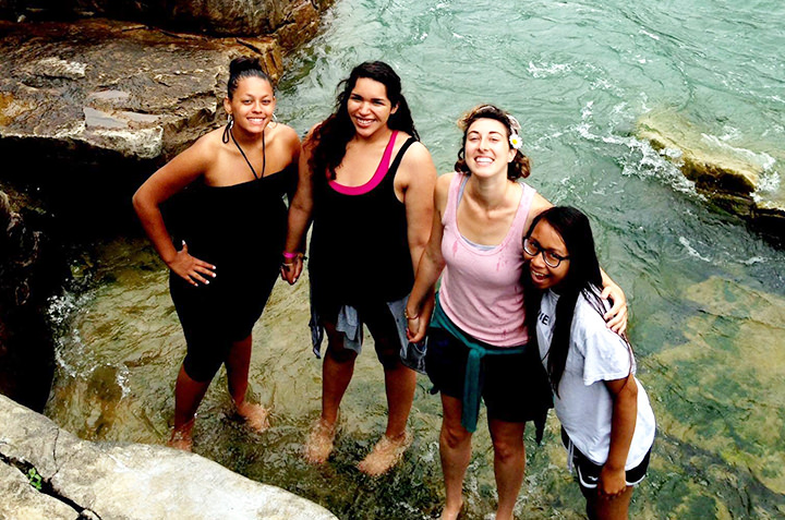 Four sociology students stand in crystal clear water on a trip abroad.