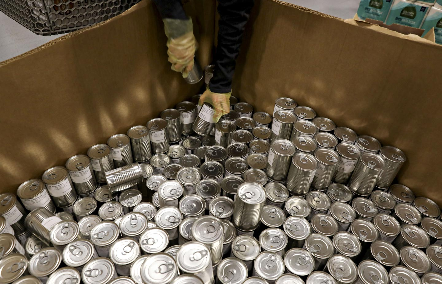 Image of cans being unloaded from a delivery box