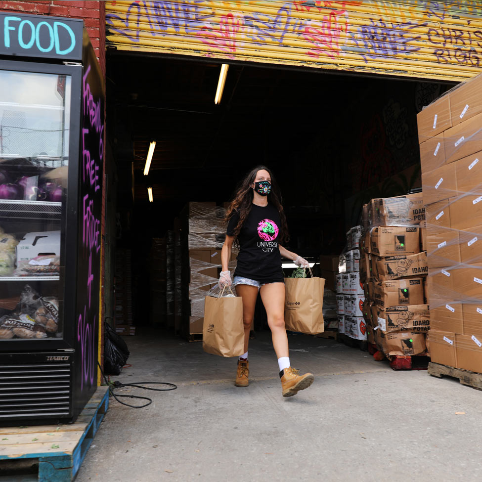 woman walking out of warehouse with bags of food in hand