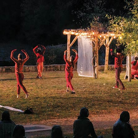 Image of masked dancers in the arboretum at night