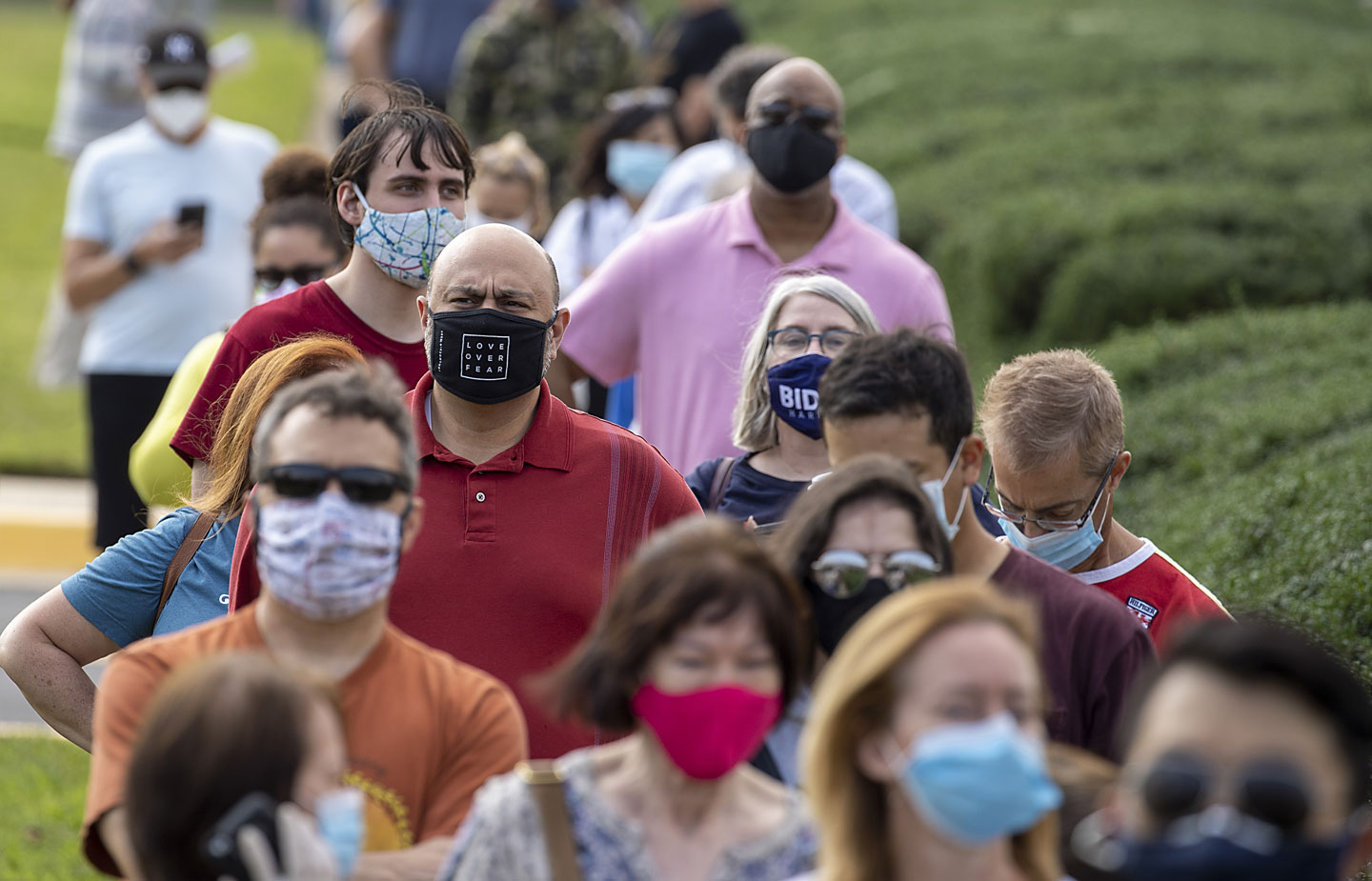 Image of people waiting in line to vote wearing masks