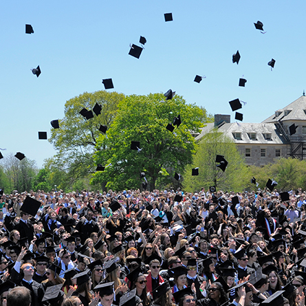 Graduating students throw up their caps in celebration.