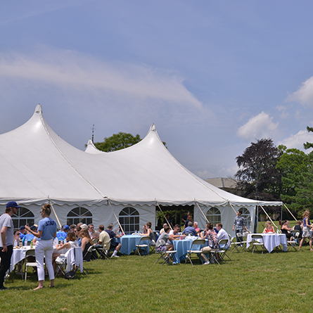 Alumni gather around the tent at Reunion.
