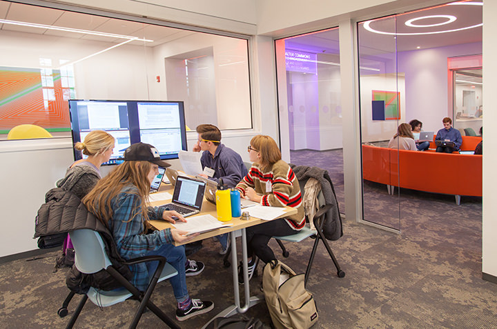 A group of students work together in the collaboration space of the Global Commons.