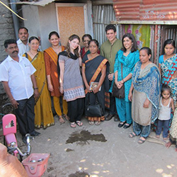 Professor Sunil Bhatia (center right, in green) visits Pune, India, as part of his work with Friends of Shelter Associates, a nonprofit he founded that has funded 600 toilets and sanitation projects in some of India's poorest regions.