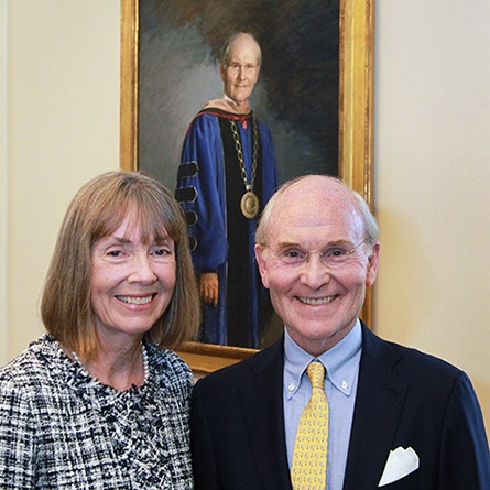 Ann Higdon and President Emeritus Leo I. Higdon Jr. in front of Higdon's official portrait in the Ernst Common Room of Blaustein Humanities Center