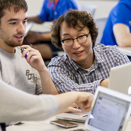 Computer Science Professor S. James Lee, right, works with a student in his