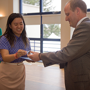 Nu Rho Psi inductee Tanya Songtachalert '18 accepts her certificate and pin from Associate Professor of Psychology Joseph Schroeder at the induction ceremony May 2.