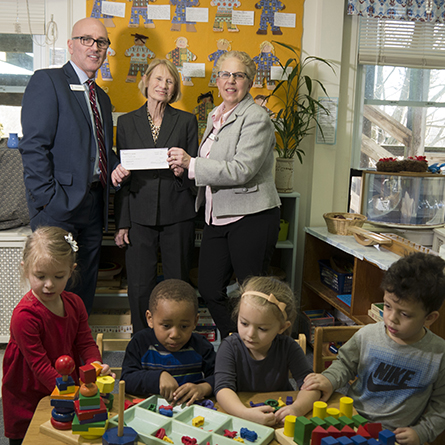 Representatives from Liberty Bank present a check to Kathryn O'Connor, director of the Children's Program, while preschool students play in front of them