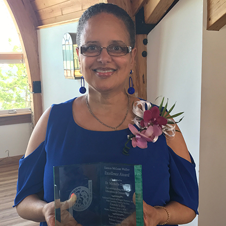 Professor Michelle Dunlap poses with award she just won