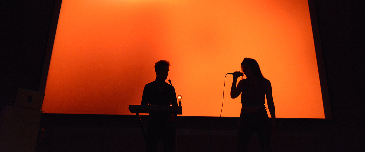 Two singers are silhouetted against a bright orange background