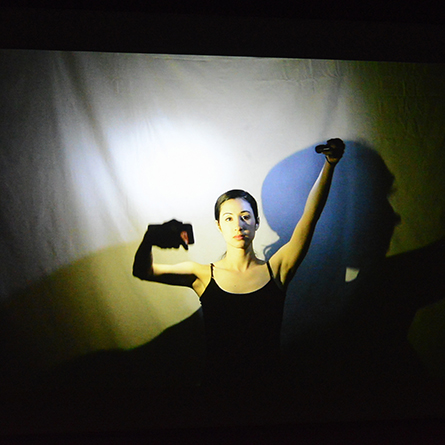A spotlight shines on a performer at the Ammerman Center performance