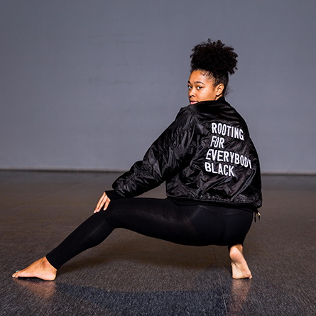 "Tanaya Cadenales '18 wears a statement jacket for her performance in ""We Are Here,"" a step piece by Jenaya Amore '19."