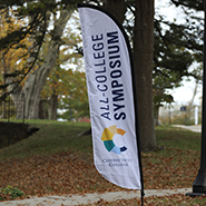 A photo of the All College Symposium banner on campus