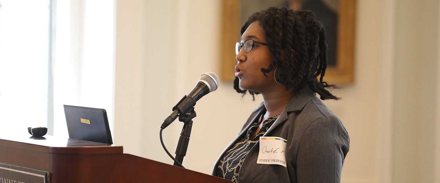 A student presents at the All-College Symposium