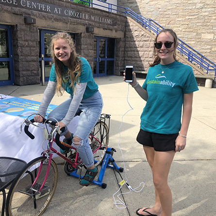 Sustainability Fellow Julia Graham '22 (left) and Senior Sustainability Fellow for Communications and Engagement Ashlyn Healey '20 demo a bike-powered charging station on the first day of Campus Sustainability Week.