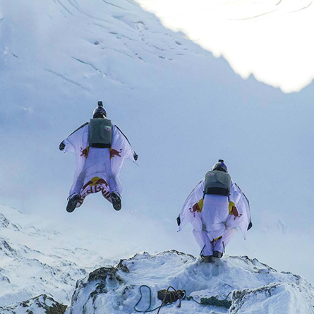 Two base jumpers on a mountainside