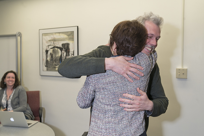 Research and Instruction Librarian Andrew Lopez hugs President Katherine Bergeron after she surprises him with the Student Support Award.