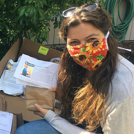 Ana Clarkson '21 with the packages of cloth masks she helped create as a team lead with Seamstresses Unite.