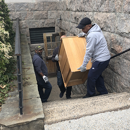 L-R: Connecticut College Facilities staff members Alexandher McQueen, Angelo Urena and Gamalier Berroa carry a dresser being donated to New London's Homeless Hospitality Center for a new isolation center for people exhibiting symptoms of COVID-19.