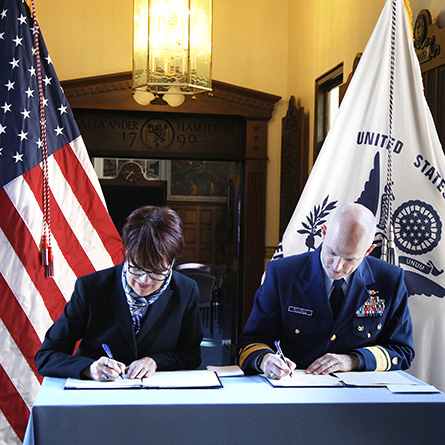 Connecticut College President Katherine Bergeron, left, and the superintendent of the U.S. Coast Guard Academy, Rear Admiral William G. Kelly, sign the new Memorandum of Agreement.