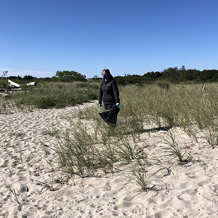 Nicole Wright '24 picks up garbage at Ocean Beach Park in New London. Photo by Winona Hunter '24.