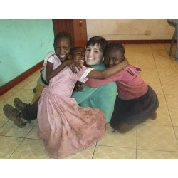 Gabby Arenge '14 poses with children in Kibera.