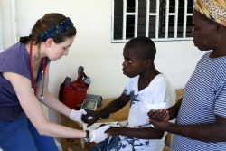 EMT Shannon Brady '14 works with a child during her spring break trip to Haiti last year.