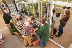 Chad Jones, the Milne Assistant Professor of Botany and Environmental Sciences at Connecticut College, left, helps first-year botany students prepare to plant seedlings in the renovated greenhouse.