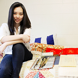 Lu Shan Zhang '14 poses with some of her calligraphy work and the supplies she brings with her to campus from China. Photo by Miguel Salcedo '14.