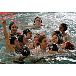 Members of the women's water polo team surround Coach JJ Addison in celebration moments after the team clinched its first league championship.