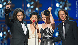 "Sean Fine '96 (far left) and Andrea Nix Fine (second from right) accept the Oscar for best documentary short for ""Inocente"" in 2013. They are joined on stage by Inocente Izucar, the subject of the film, and film editor Jeff Consiglio."