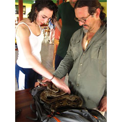 Emma Sherer '13 (left) and Associate Professor of Ethnobotany Manuel Lizarralde check out a six-foot boa constrictor they caught in Belize.