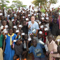 Brigid O'Gorman '11 poses with children from the Asayo's Wish Orphanage in Kaberamaido, Uganda. The children are showing off their new clinic cards.