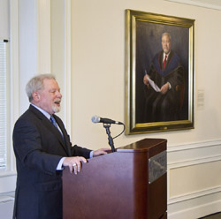 President Emeritus Norman Fainstein speaks in front of his official presidential portrait.