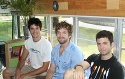 Tyler Dunham '09, left, with friends on their bus powered by vegetable oil