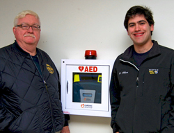 EMT instructor Chuck Holyfield (left) and EMS club president Ben Allar '13 with Connecticut College's new Automated External Defibrillator (AED)