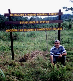 RTT forester Rolando Camacho kneels in front of the sign dedicating the new Connecticut College Klinki Plantation to the memory of Dr. William A. Niering.