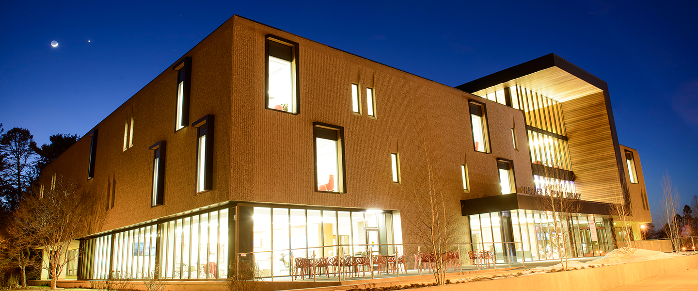 The lights are on at night in the Shain Library